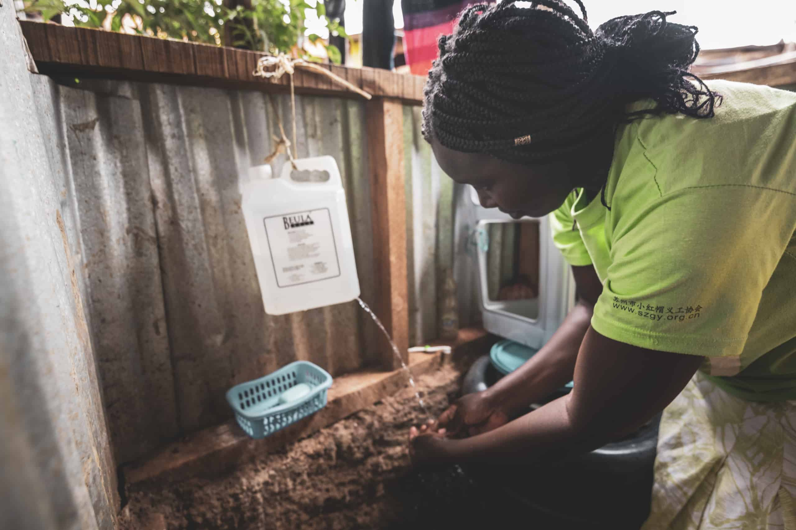 A woman washes her hands at a makeshift handwashing station with a water jug.