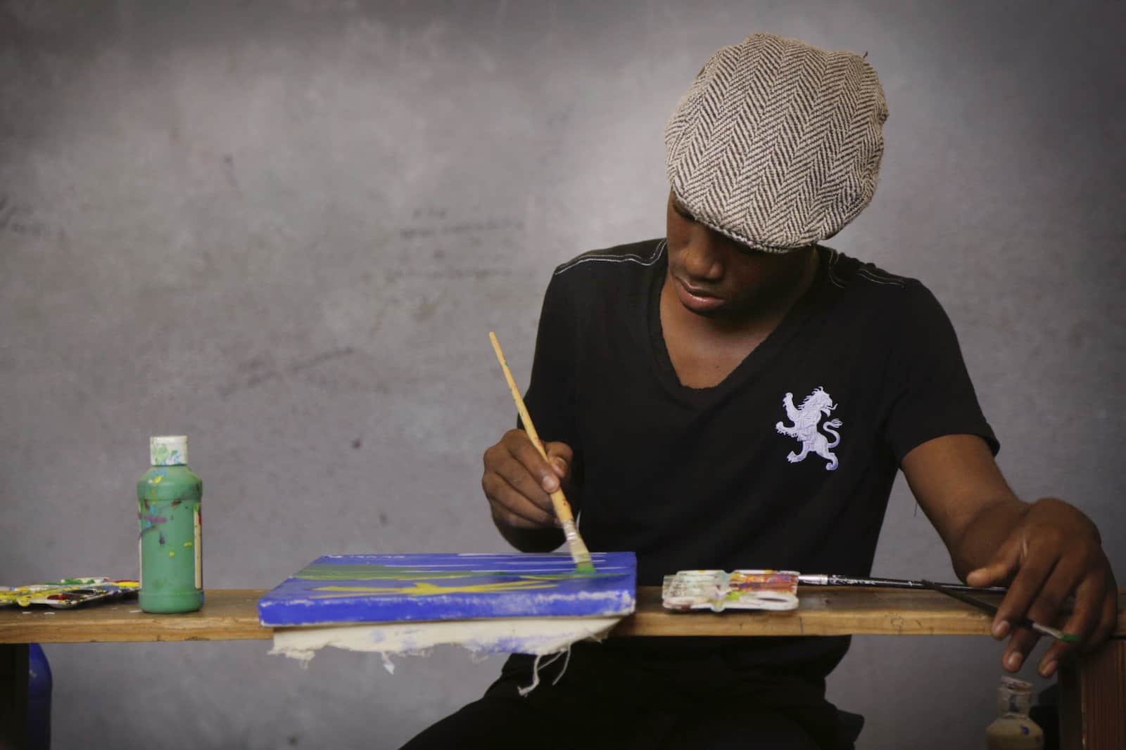 A man in a grey beret sits at a table, painting.
