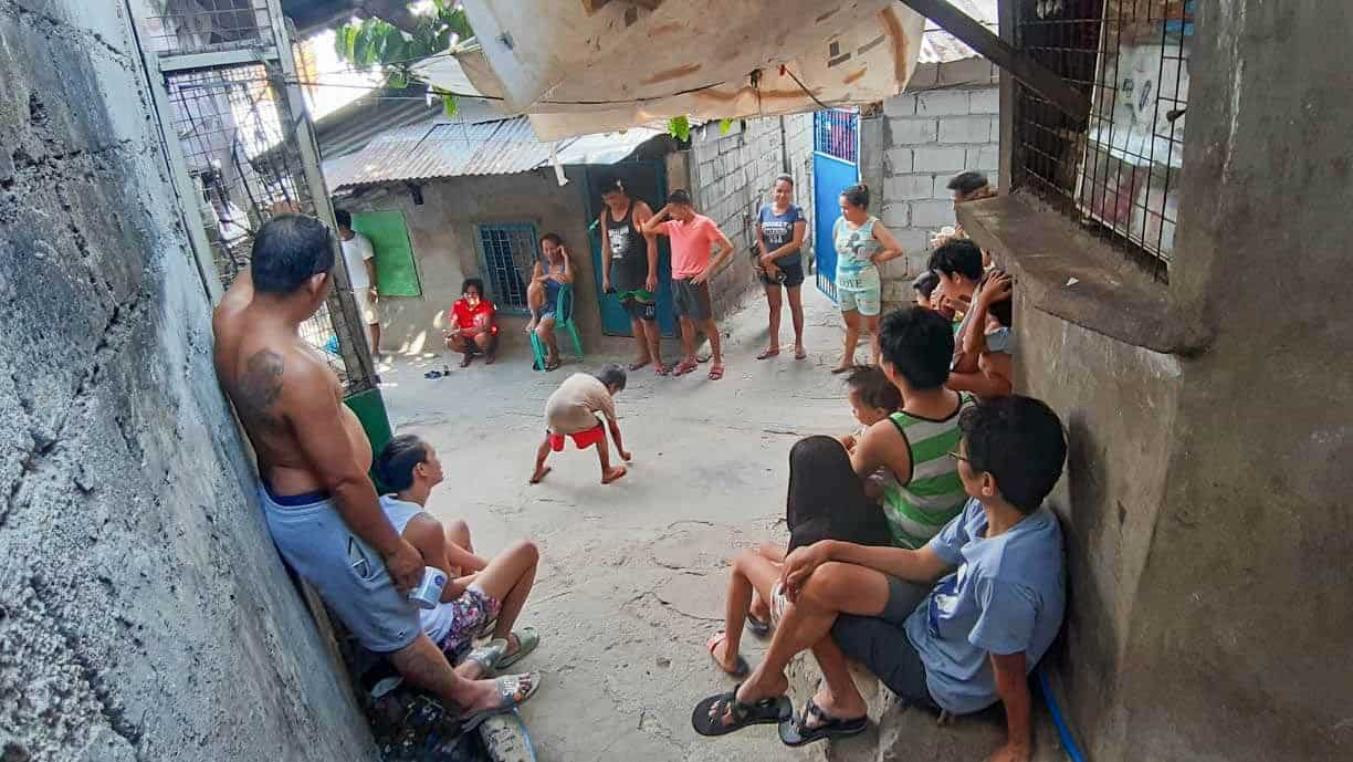 People sit outside their homes in a slum in Cebu City where they are supposed to be social distancing.