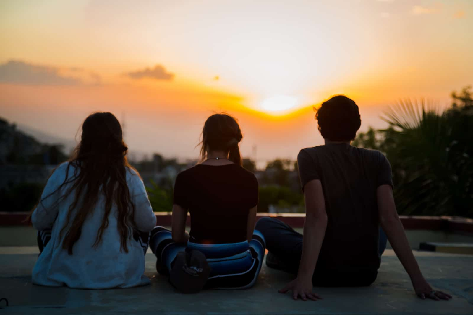 Three people sit cross-legged in front of a sunrise.
