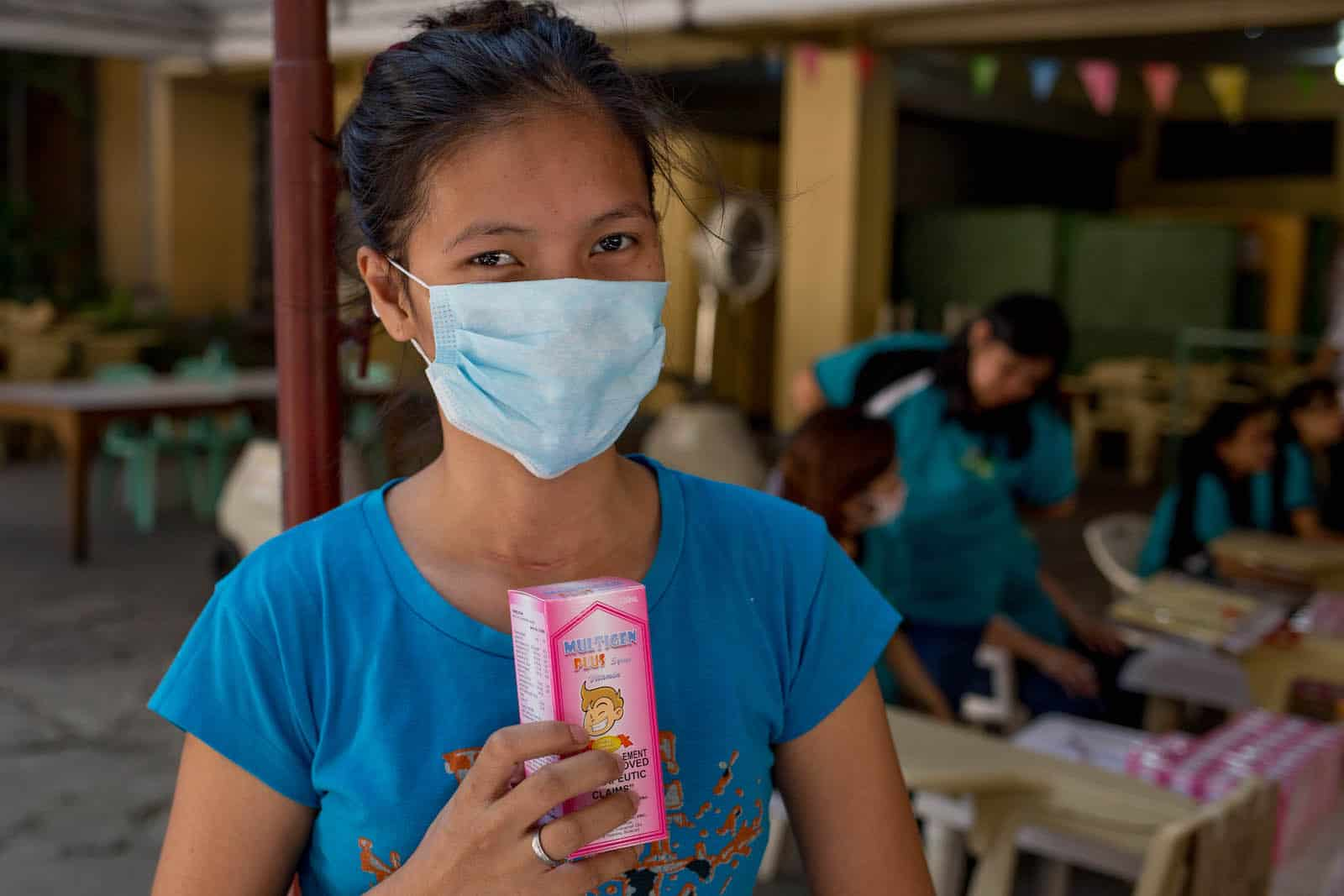 A young woman wearing a face mask holds a box of vitamins