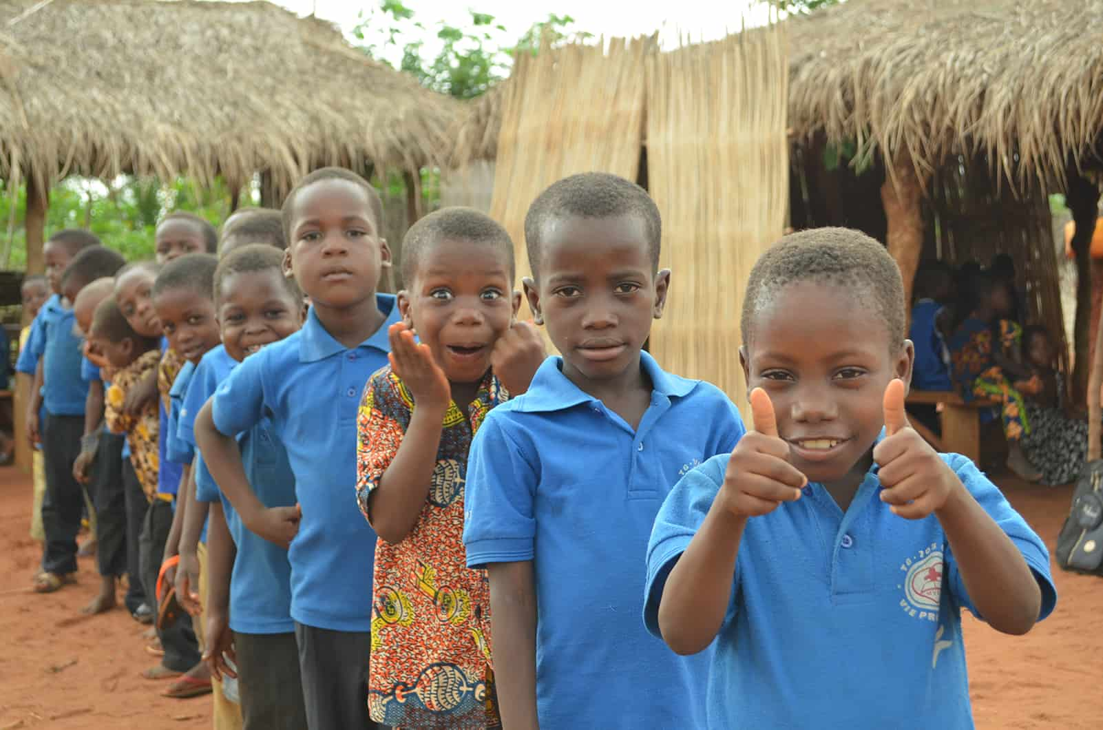 A line of kids in togo with one making a funny face
