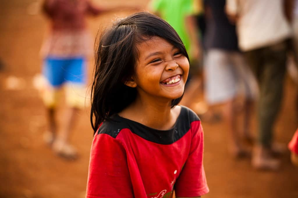 A little girl wearing a red shirt smiling so big her eyes are closed
