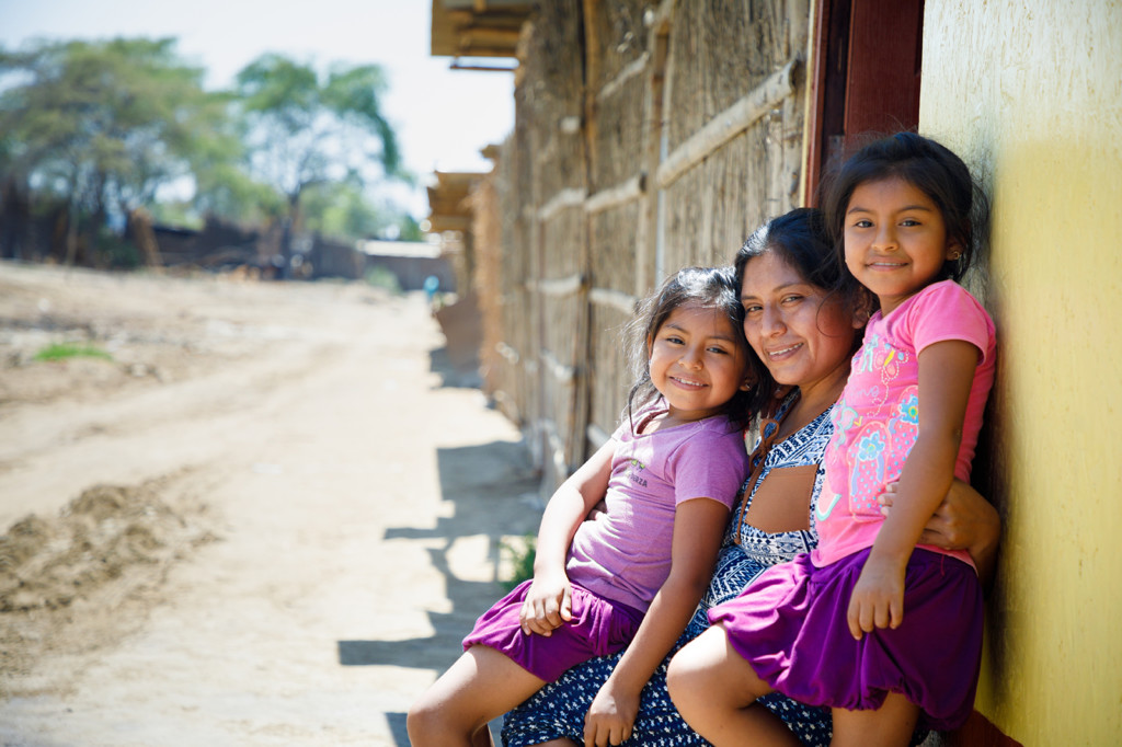 A happy mother and her children sitting by a wooden building