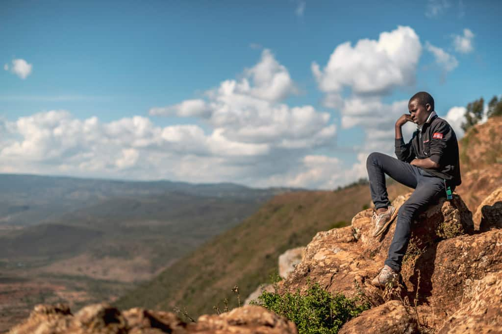 Boy sitting on an outcropping of rocks looking into the distance