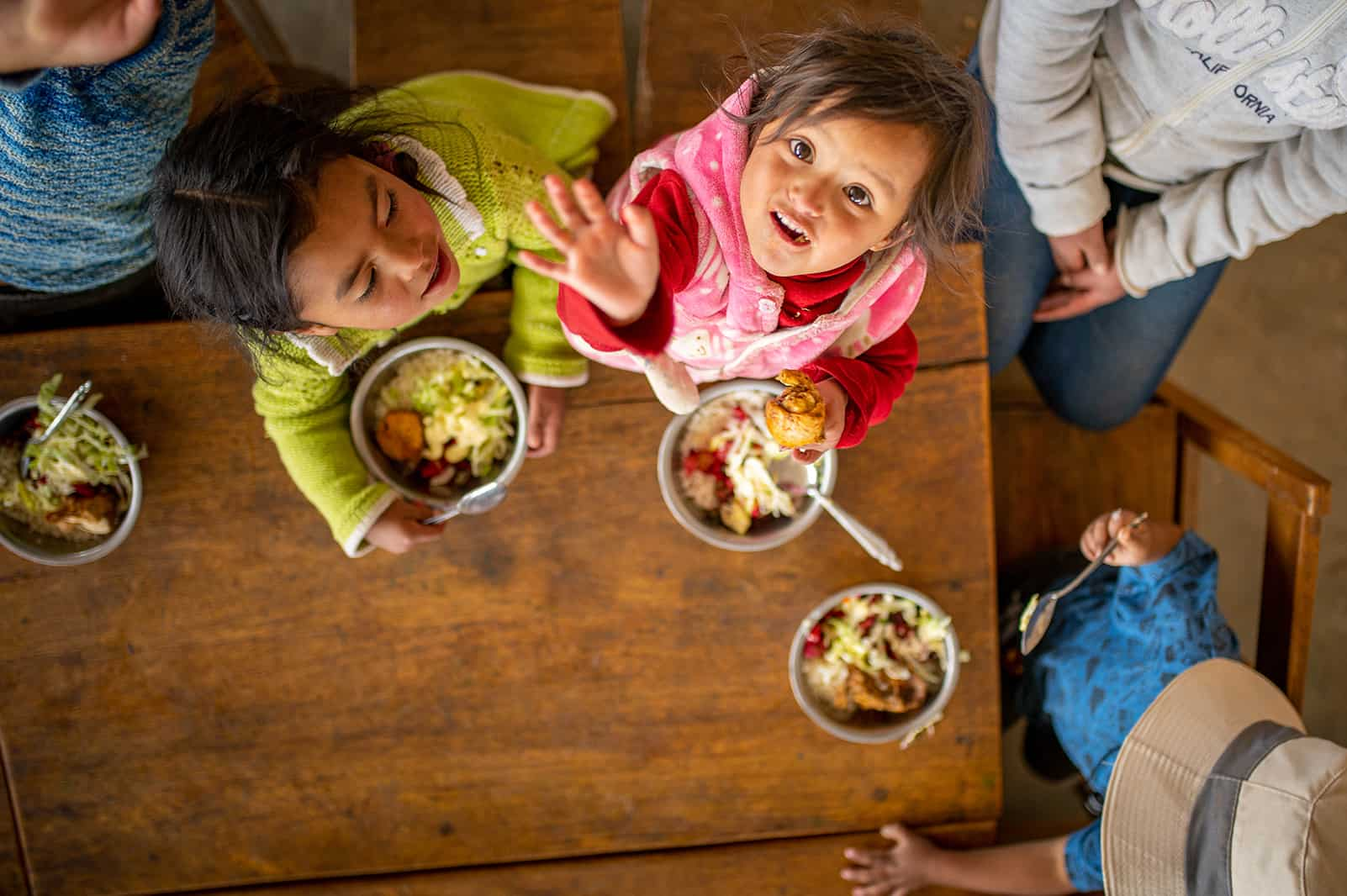 Children at a table eating looking at the camera above their heads