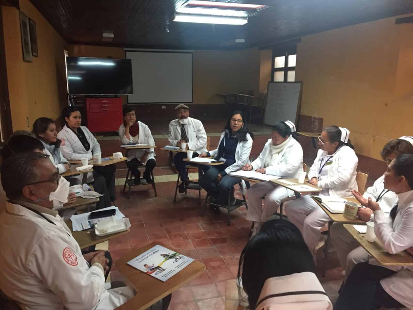 Doctors sitting at desks in a circle talking