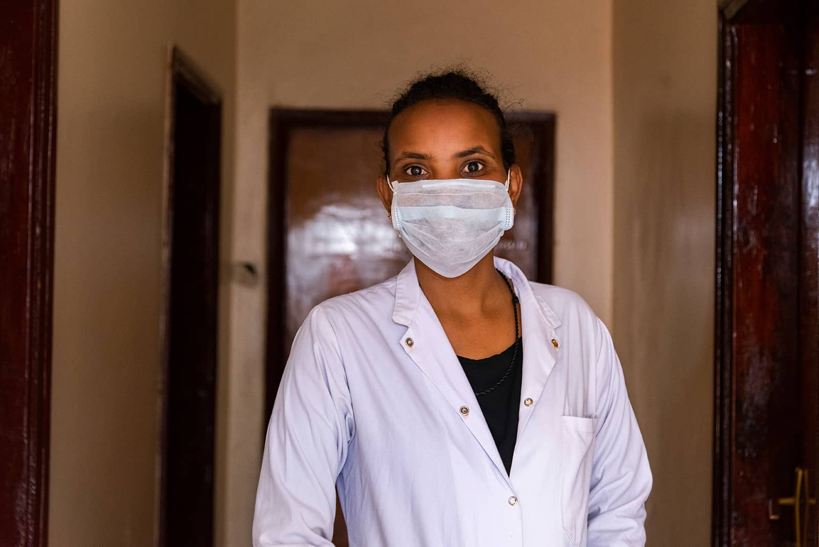 Dr. Addisalem Gebresilassie wearing scrubs and surgical mask