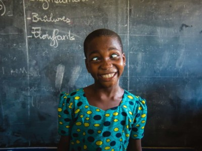 Girl from Togo in front of a chalkboard making a funny face
