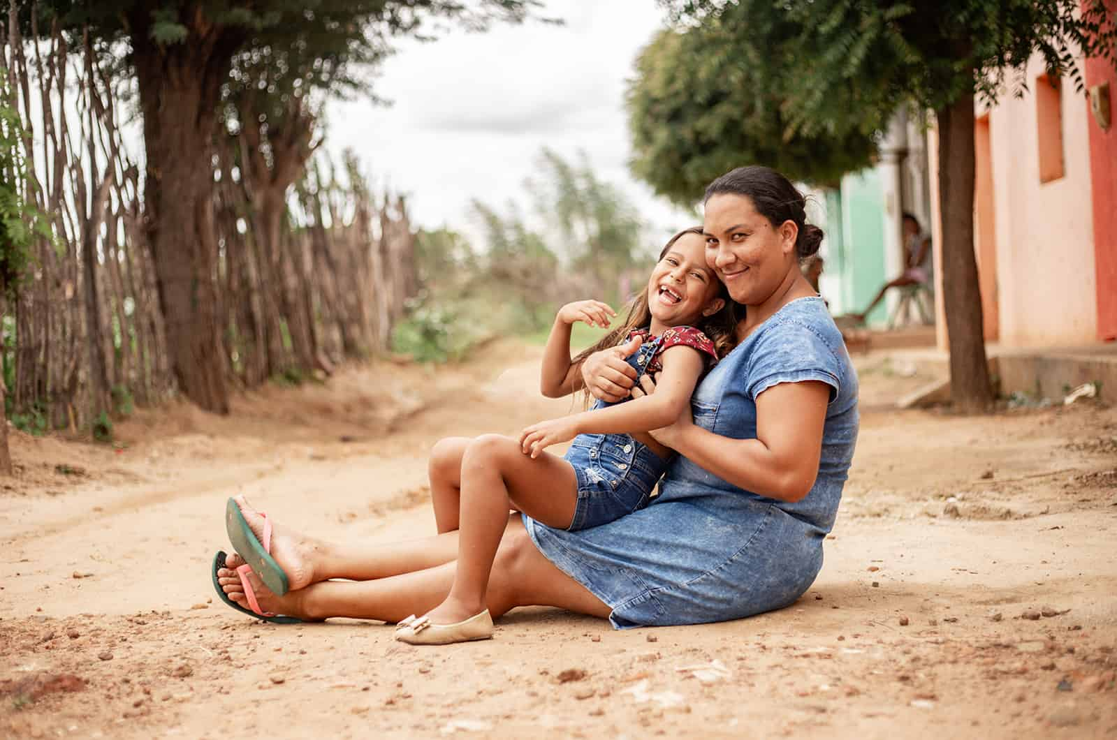 Happy mother and daughter sitting on the ground
