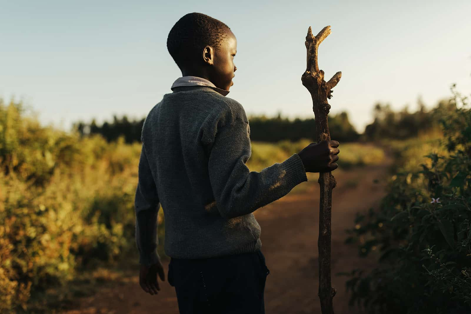 Kenyan boy walking a path with a walking stick