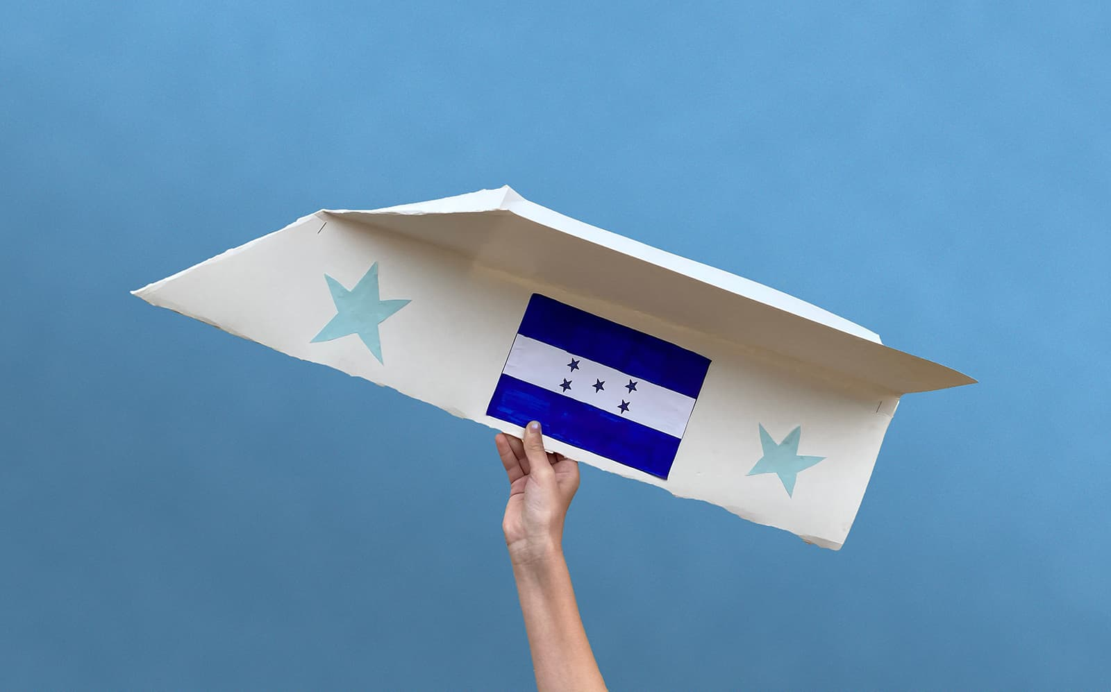 Fun family activities at home: Large paper airplane decorated with Honduran flag