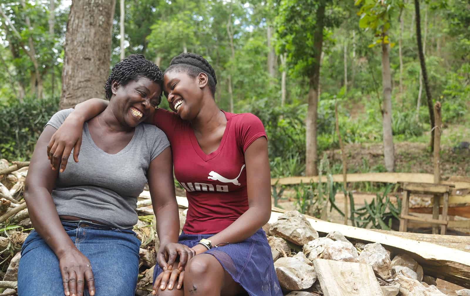 Laughing mother and daughter sitting on a rock wall