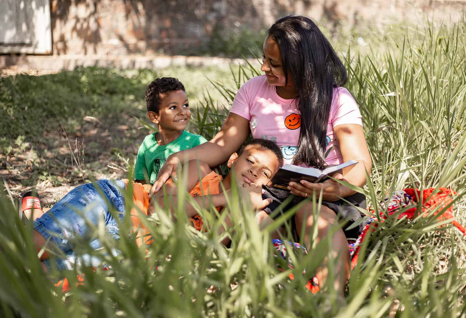 Mother and children reading in the grass