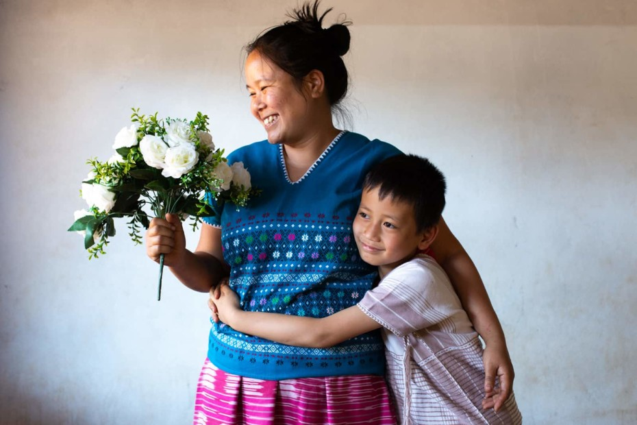 Mother holding flowers with child hugging her