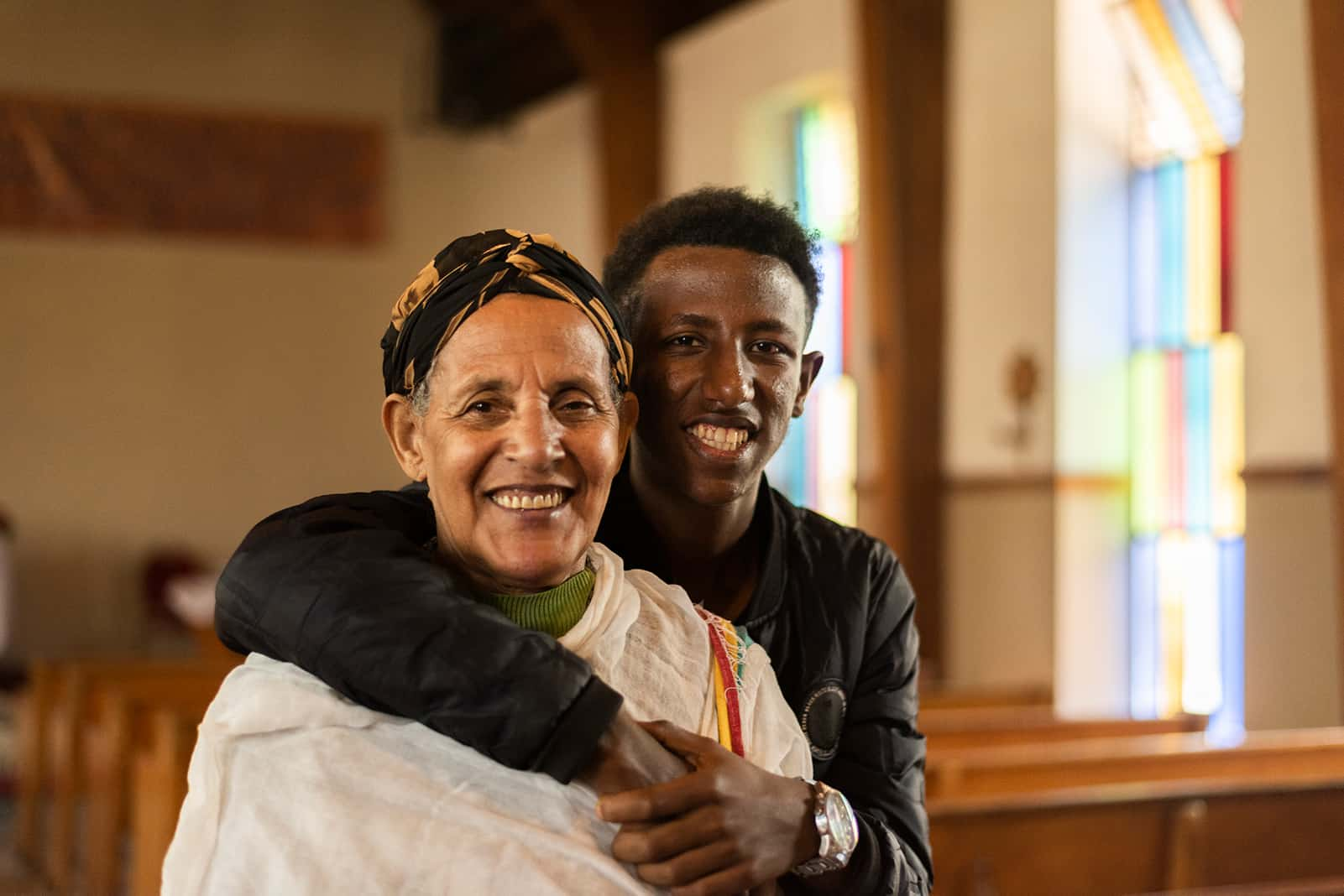 Son hugging mother in a church