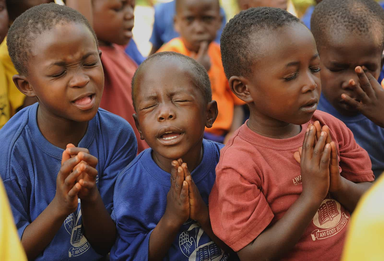 Three boys from Uganda fervently praying