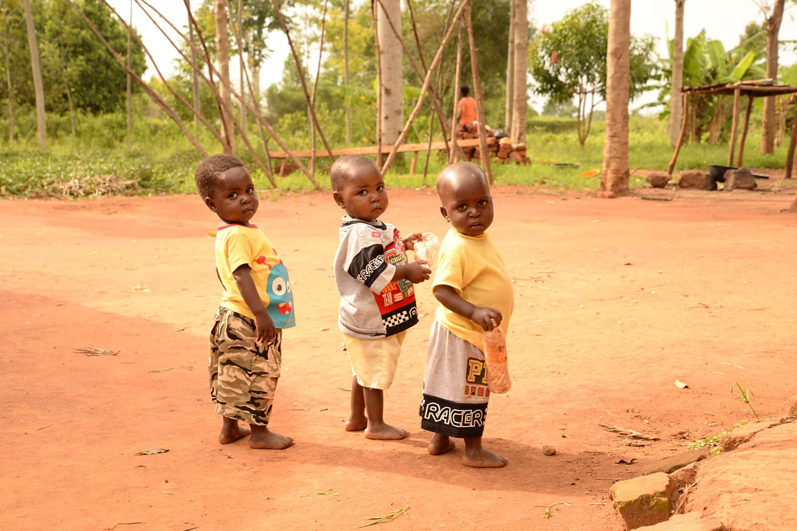 Toddler triplets on a dirt road in Uganda