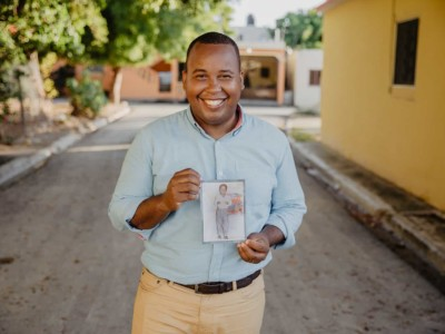 Tony Beltran holding a picture of himself when he was a child
