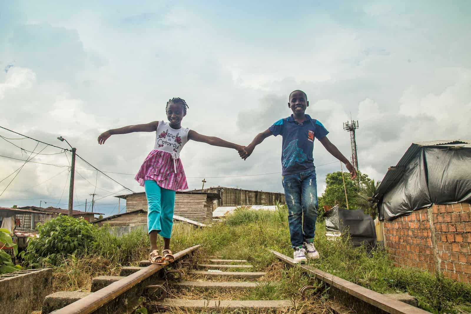 Two children holding hand walking along railroad tracks
