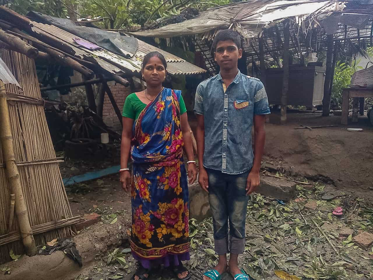 A boy and woman stand in front of a home damaged by Cyclone Amphan