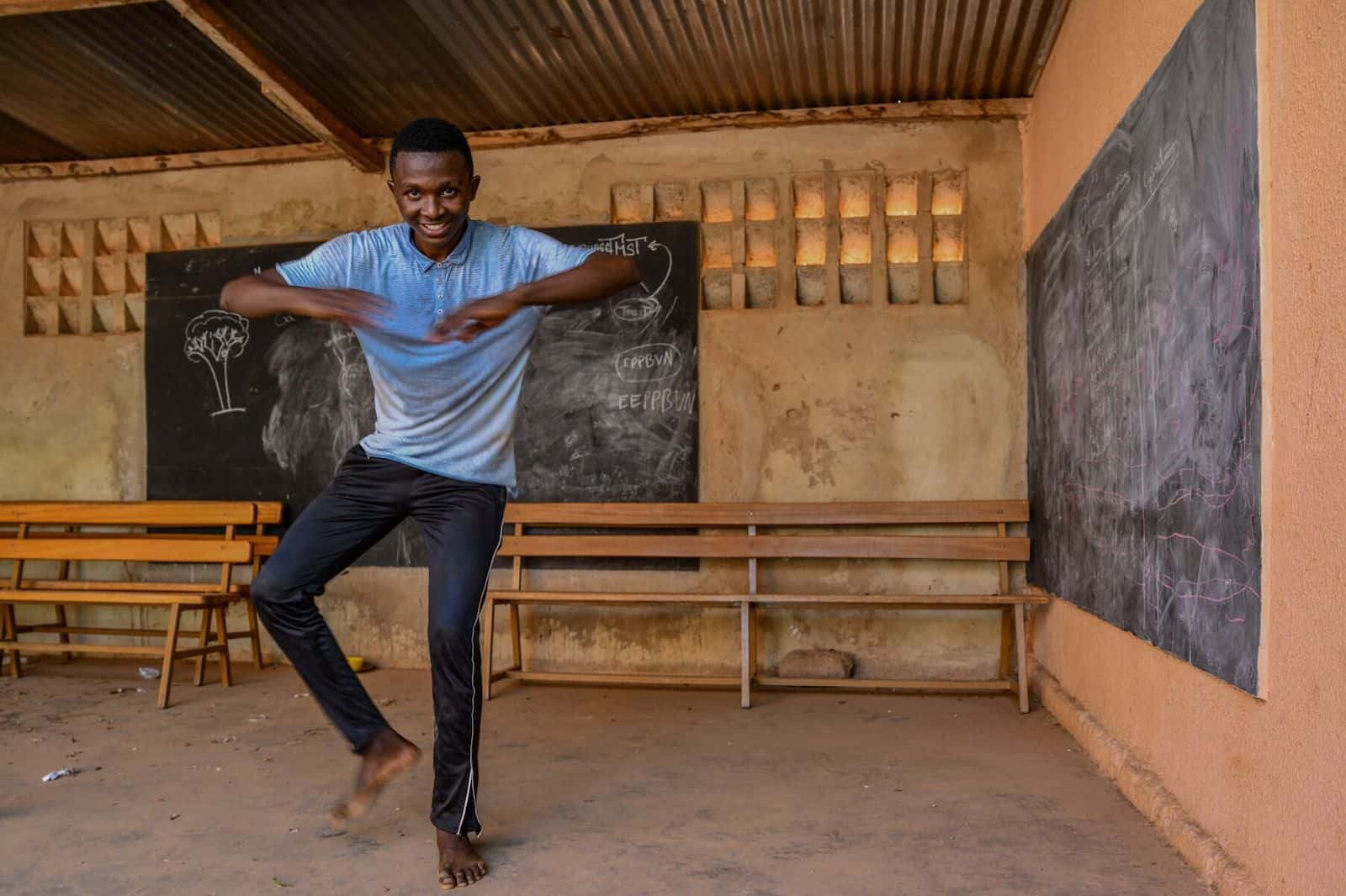 A young man dances in a classroom.