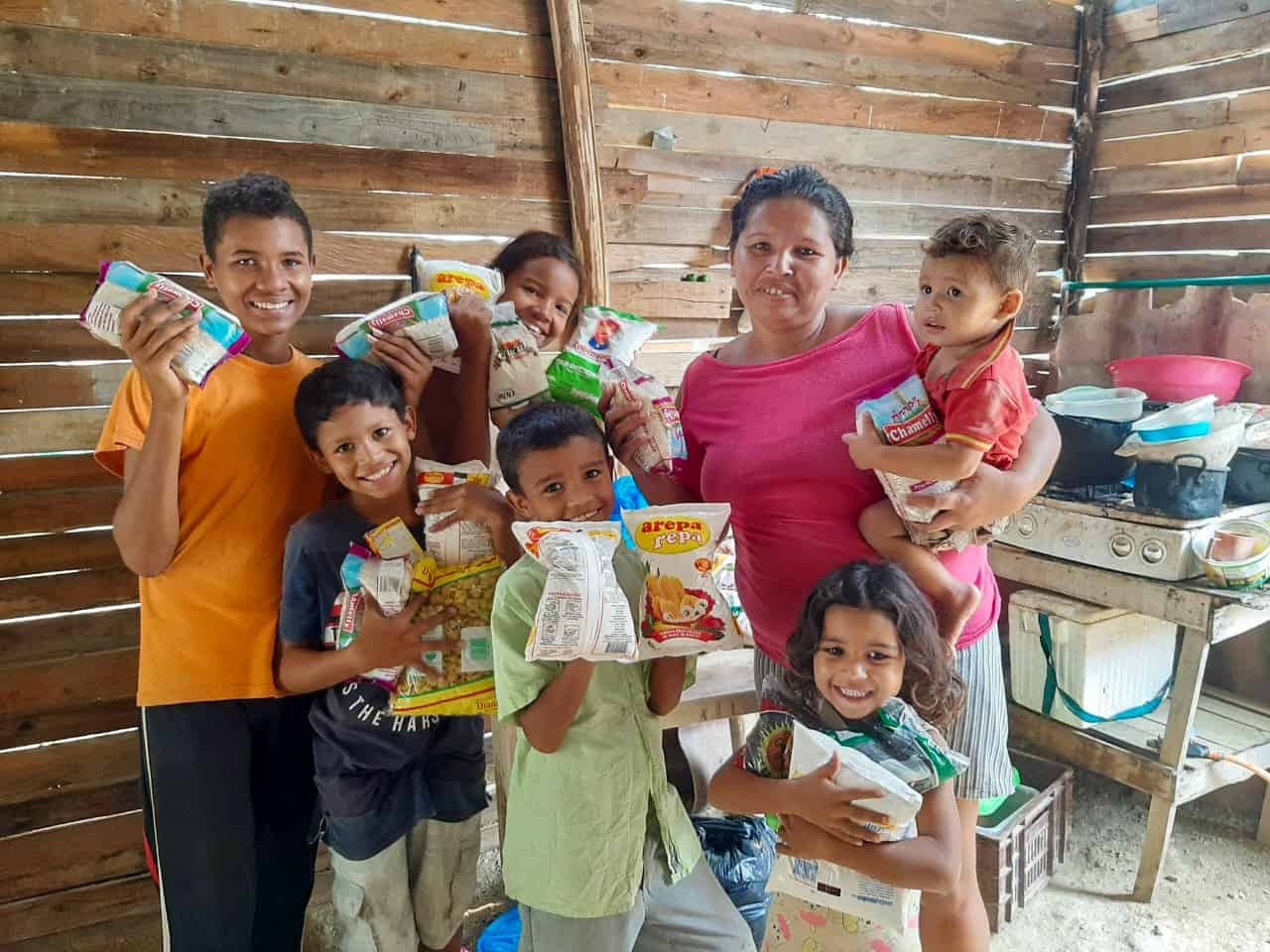 A family holds packages of food.