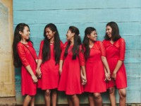 Five girls wear red dresses, laughing and standing in front of a green wall