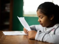 A girl reads a letter.