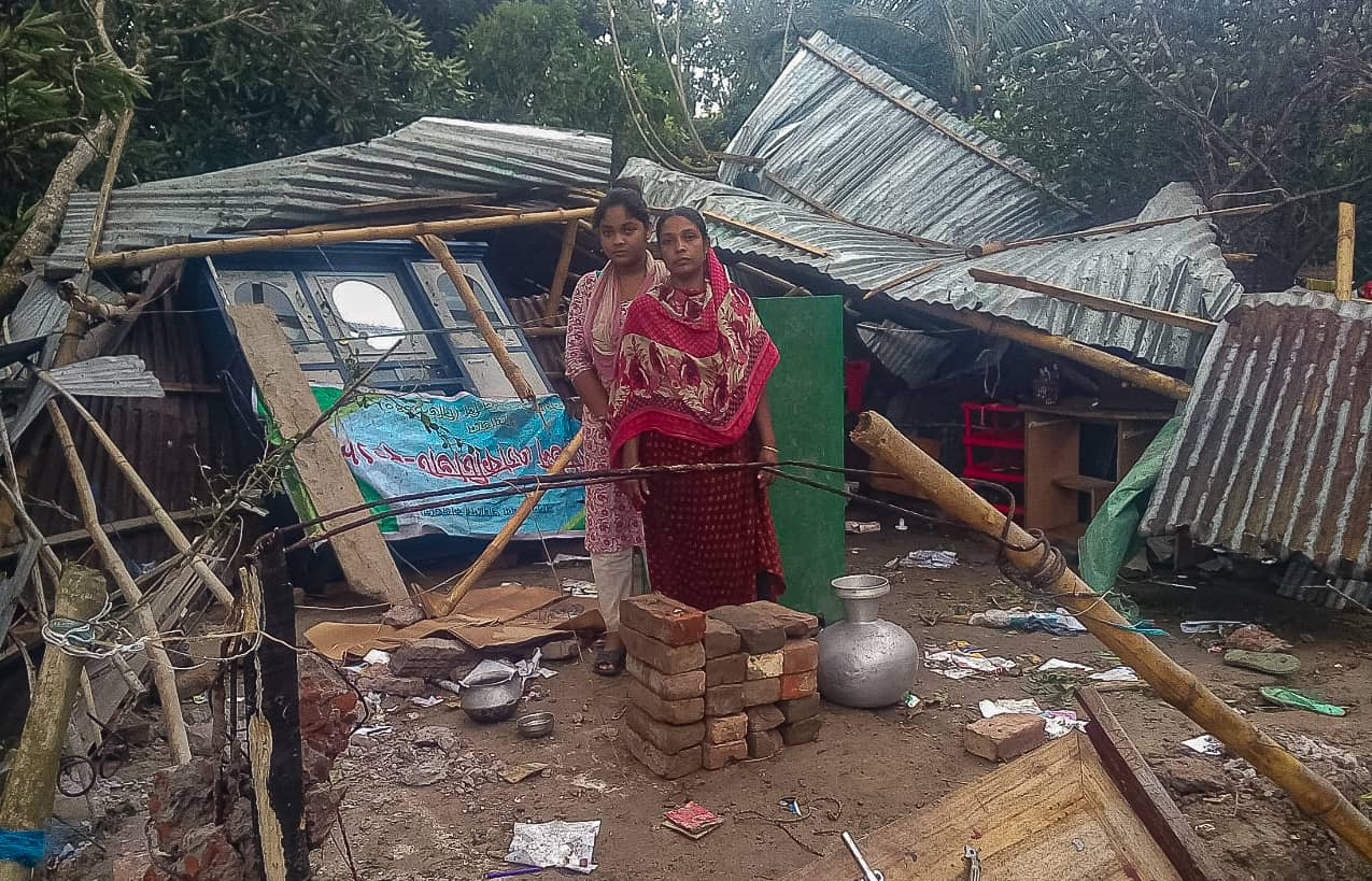 A girl and a woman stand in front of a home destroyed by Cyclone Amphan.