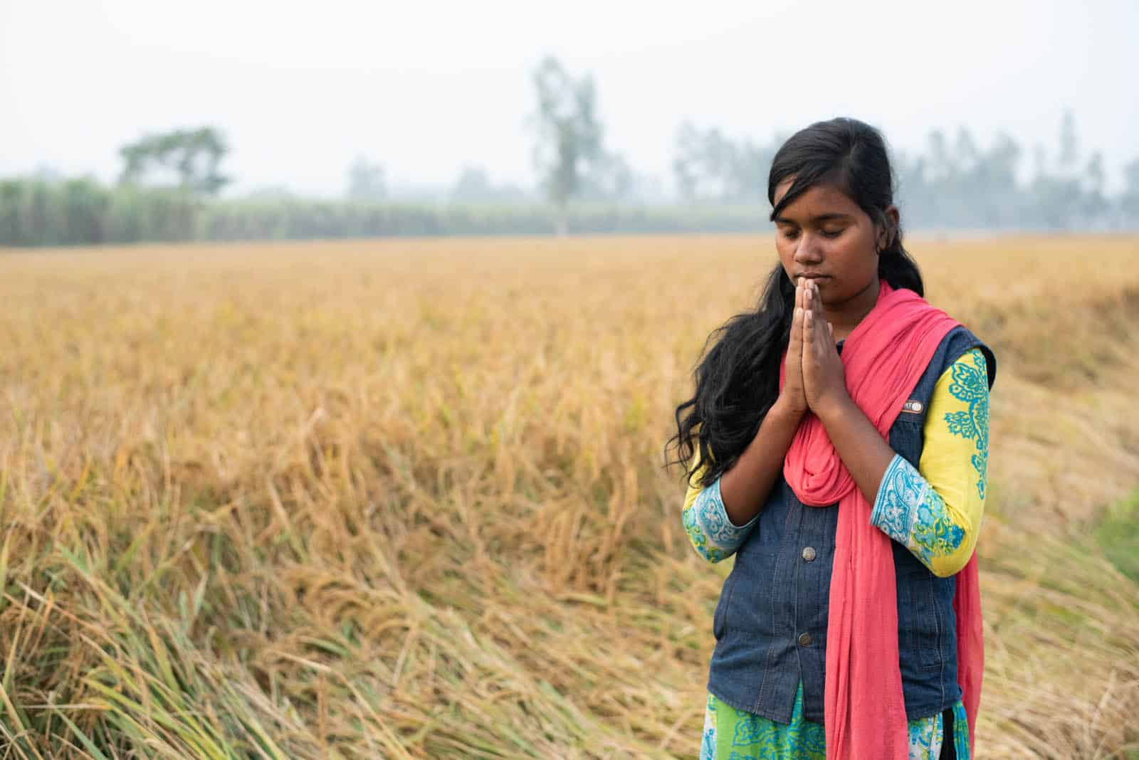 Angela praying in a field