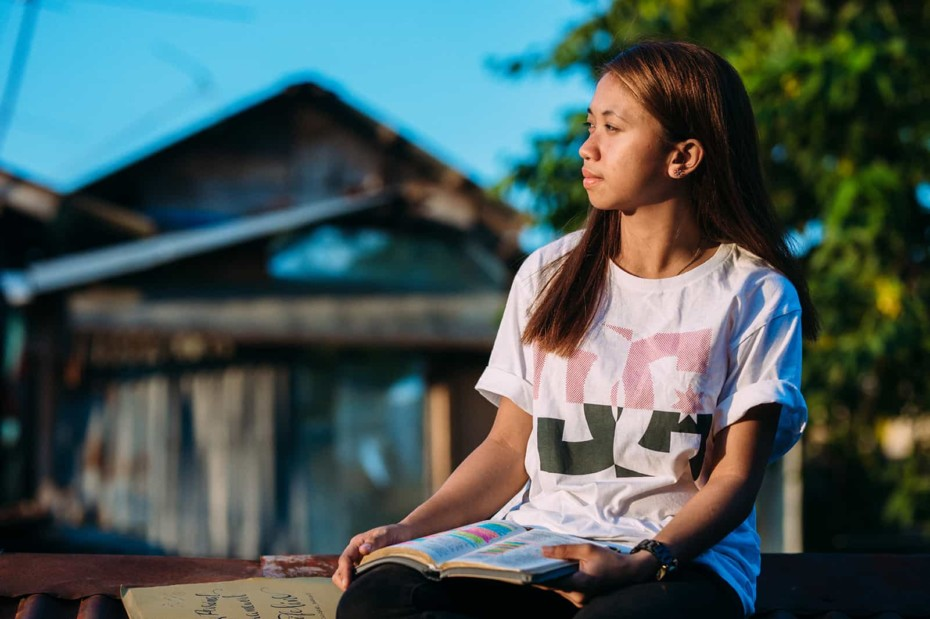 girl in a white shirt sitting outside with a book open on her lap