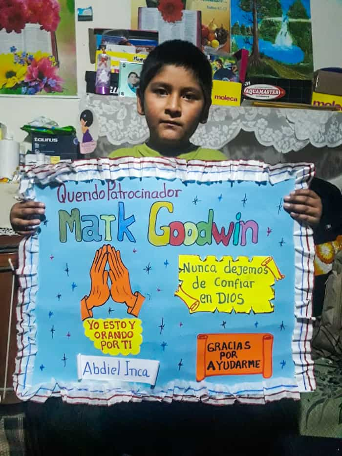 A boy holds a poster with praying hands on it and Spanish words.