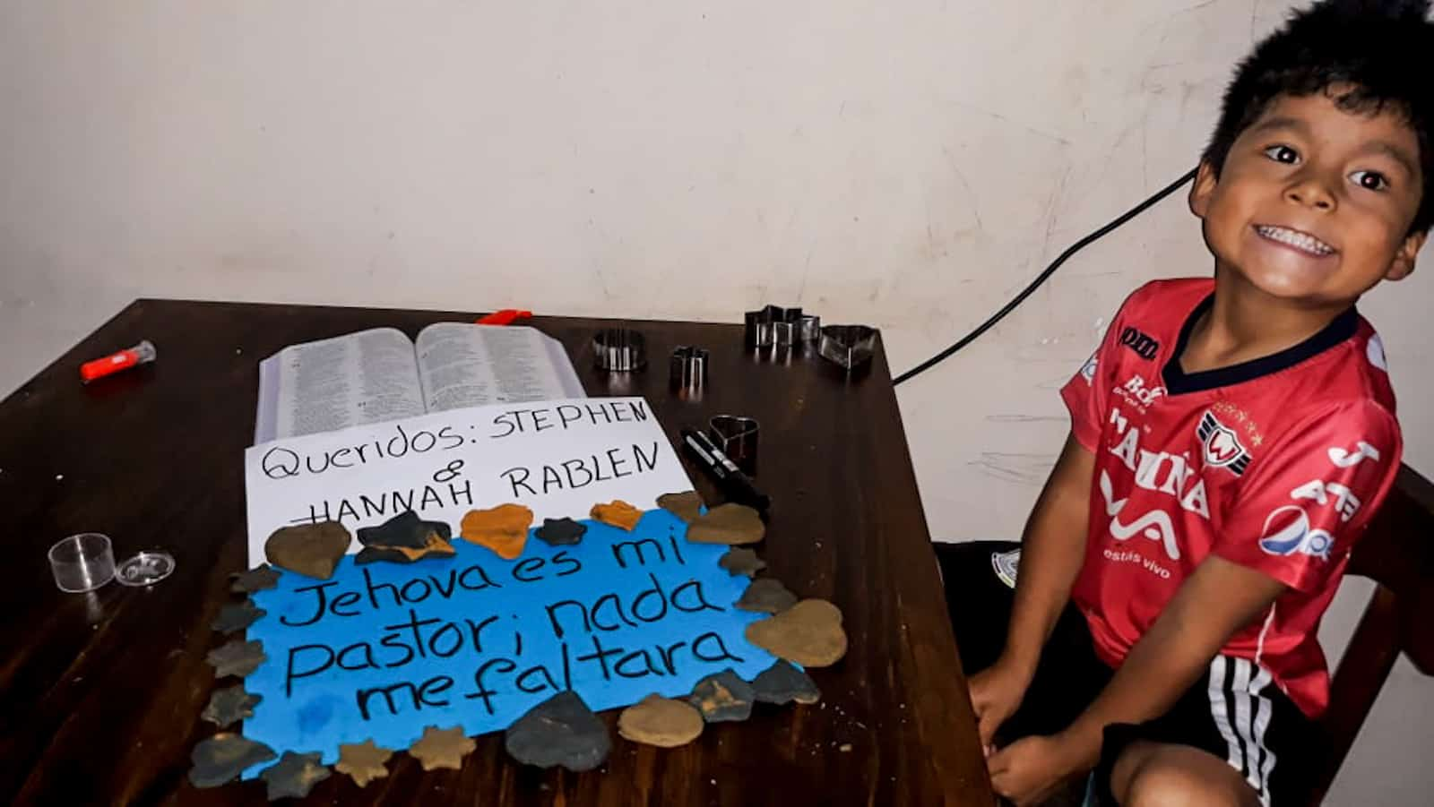 A boy sits by a table with a sign in Spanish