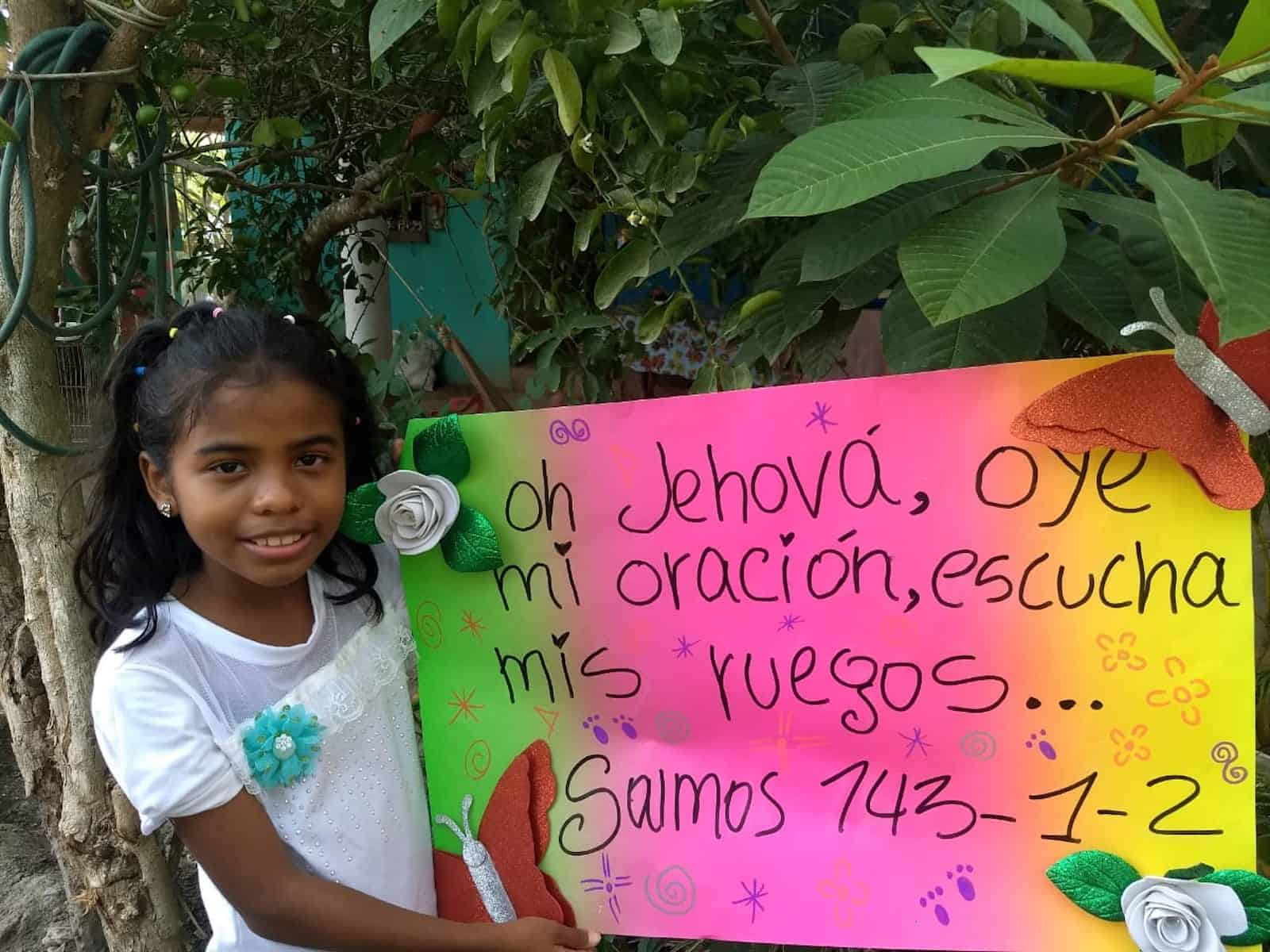 A girl holds a poster with a Bible verse written on it in Spanish.