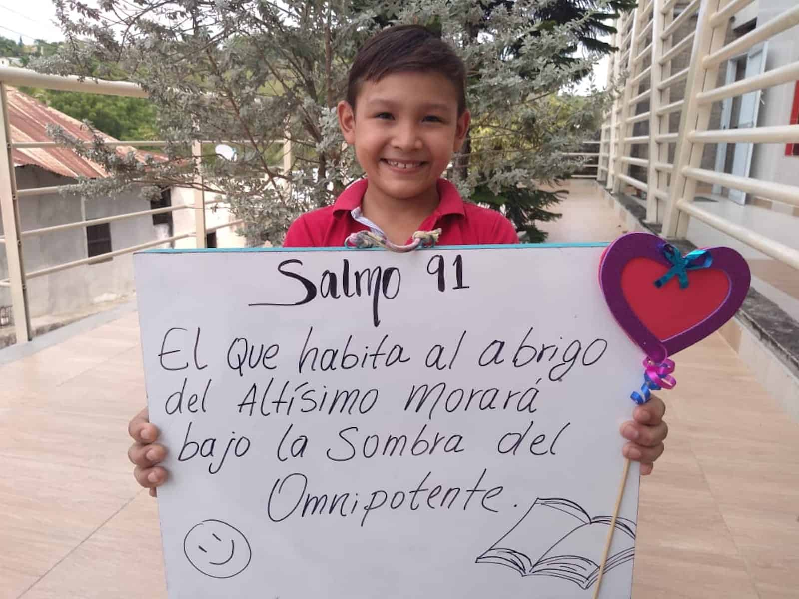A boy holds a poster with a Bible verse written on it in Spanish.