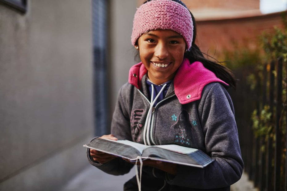 A girl in a pink hat holds a Bible.