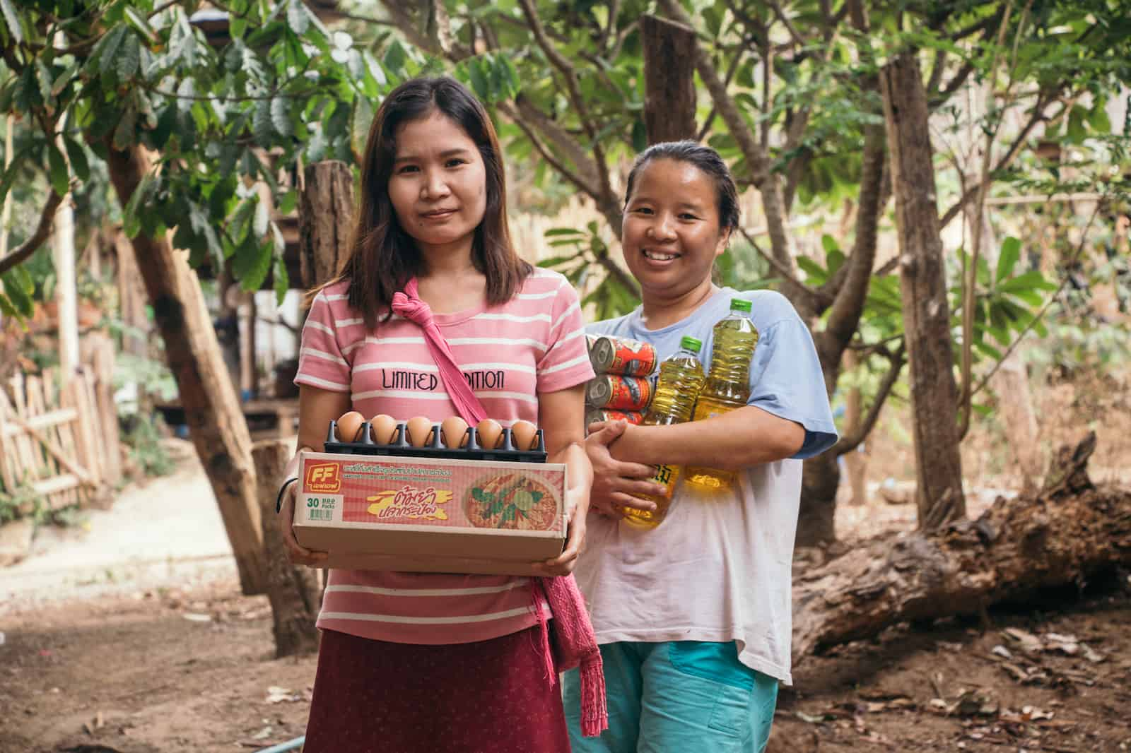 Two women holding an armful of food.