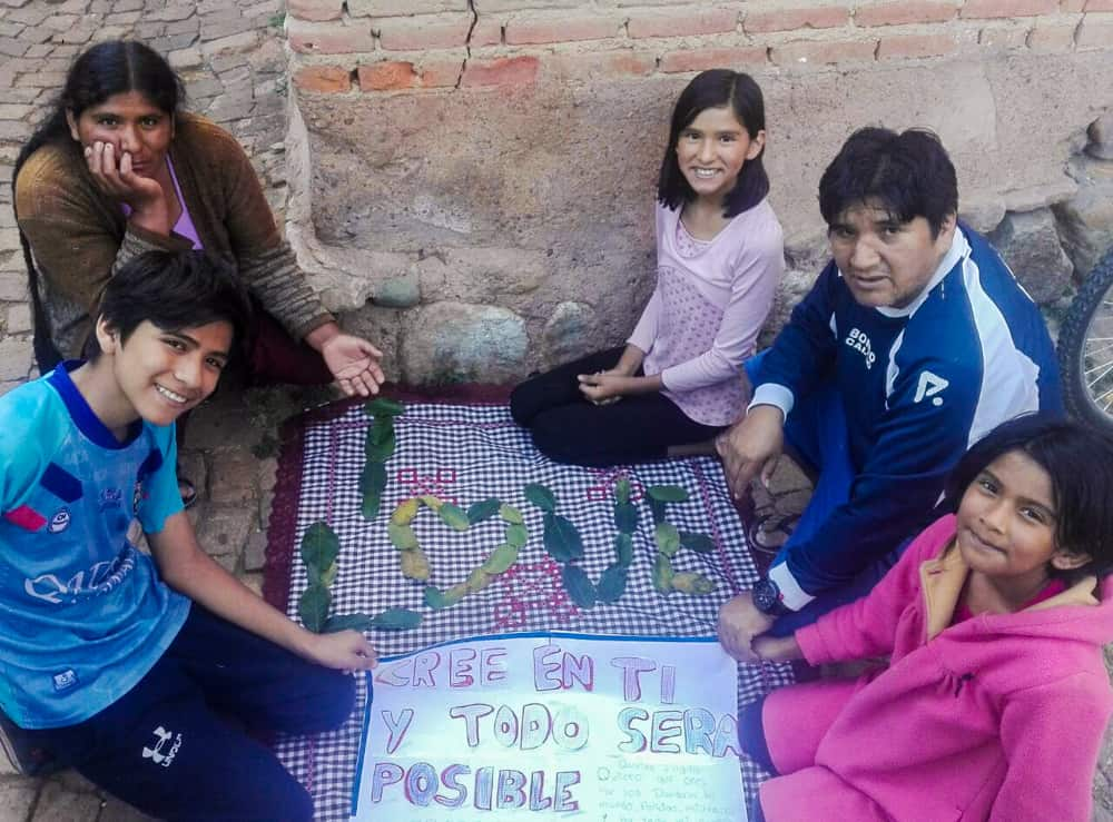 A family sits around a handmade sign