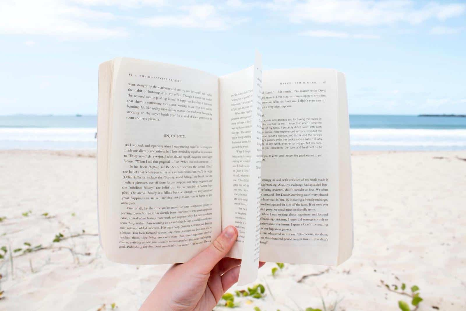 A hand holds a book on a beach