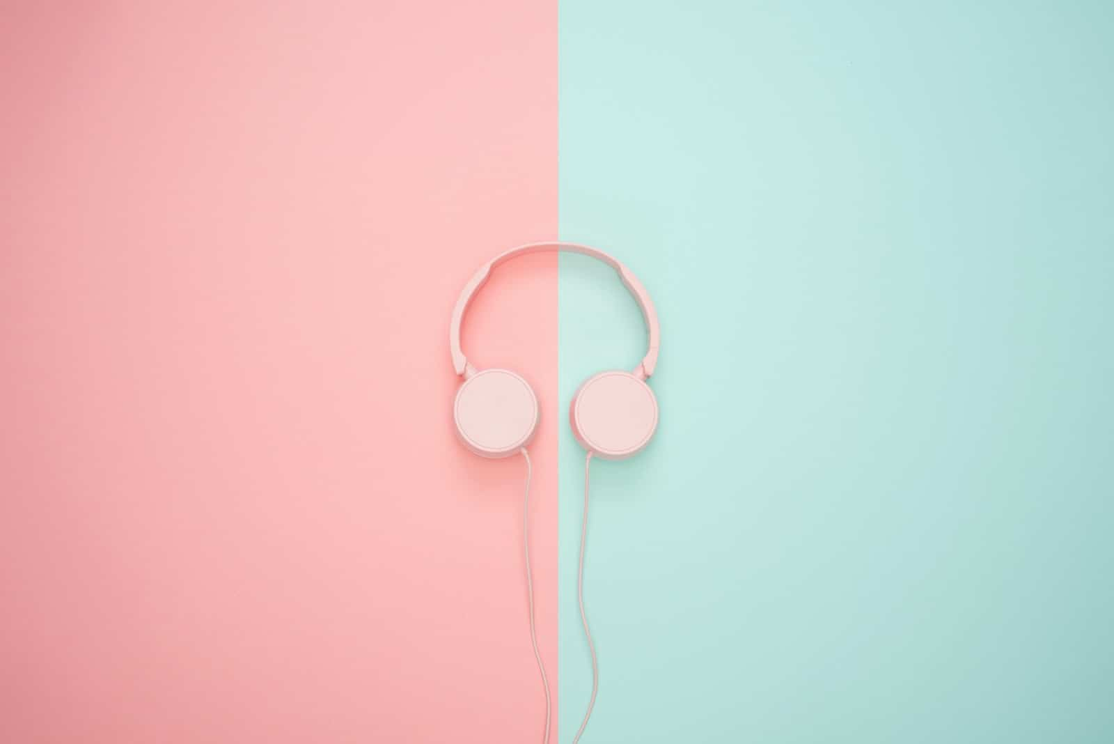 Pink headphones on a pink and green background