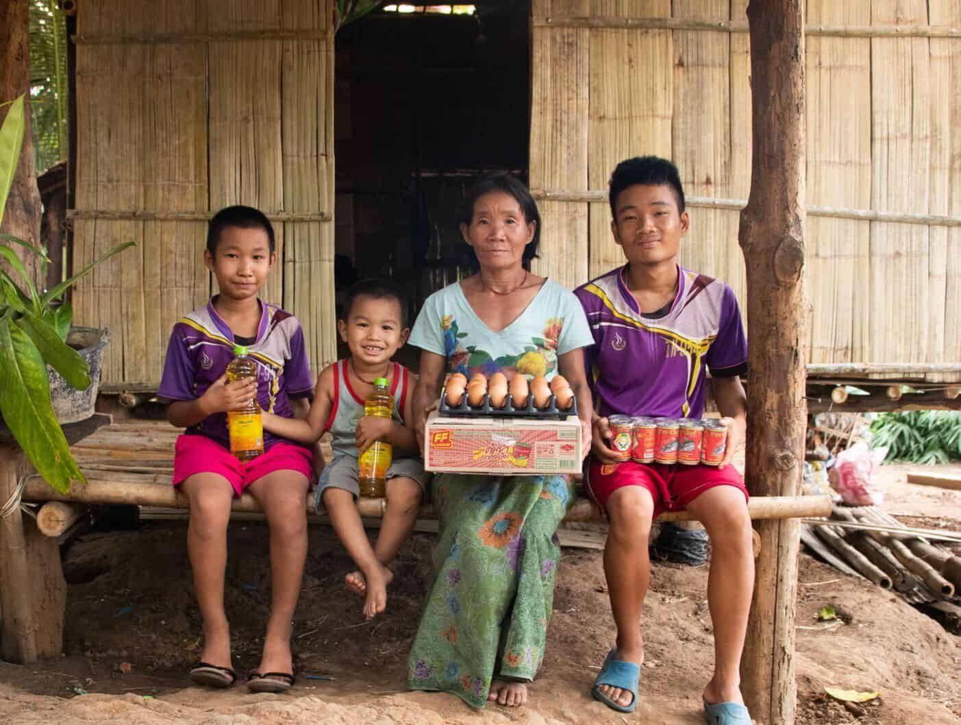 A woman and three children hold food in their laps.