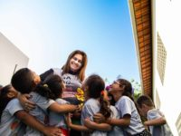 A woman is surrounded by children, hugging her.