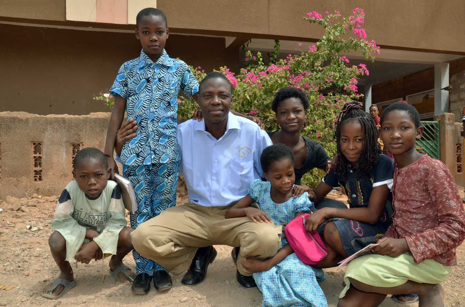 Burkina Faso National Director Ouali Palamanga. He is kneeling down, surrounded by children. They are in front of a brown building.