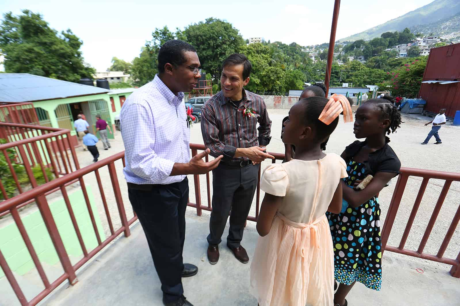 Edouard Lesege and Jimmy Mellado talk with three young girls at the project. They are all dressed up in their best clothes.