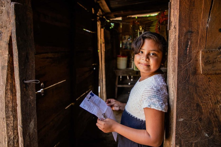 Young girl wearing a dress with a white bodice and a black skirt. She is standing in an open doorway of her home and she is holding a letter from her sponsor.