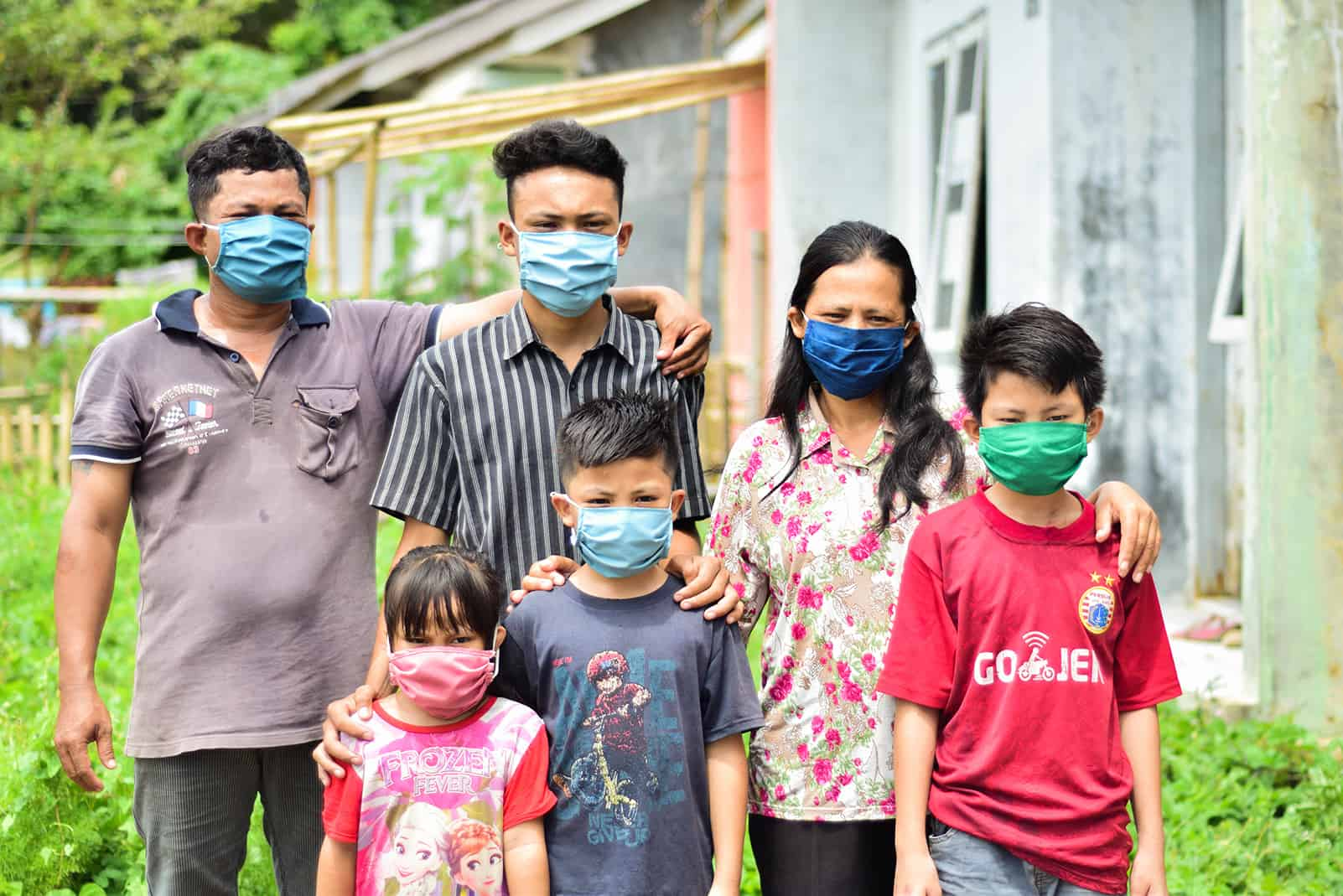 Julius and his family are standing outside of their house and are all wearing masks.