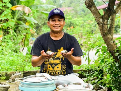 Julius is wearing a black shirt and a navy hat. He is holding two fish. In front of him are fish on a bucket that he will sell in his neighborhood. Behind him are trees.