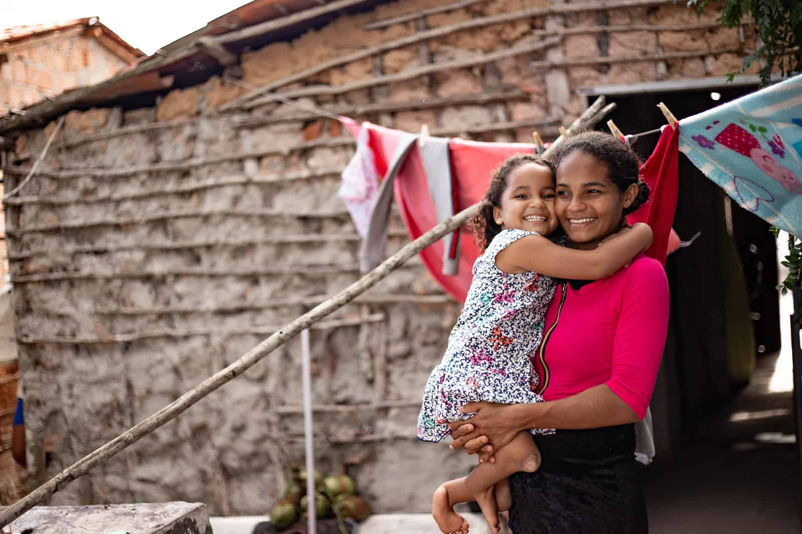 Maisa, in a blue and white dress, and her mother, Ana, in a hot pink shirt, are outside their home. There is laundry handing on a clothesline behind them. Ana is holding her daughter.