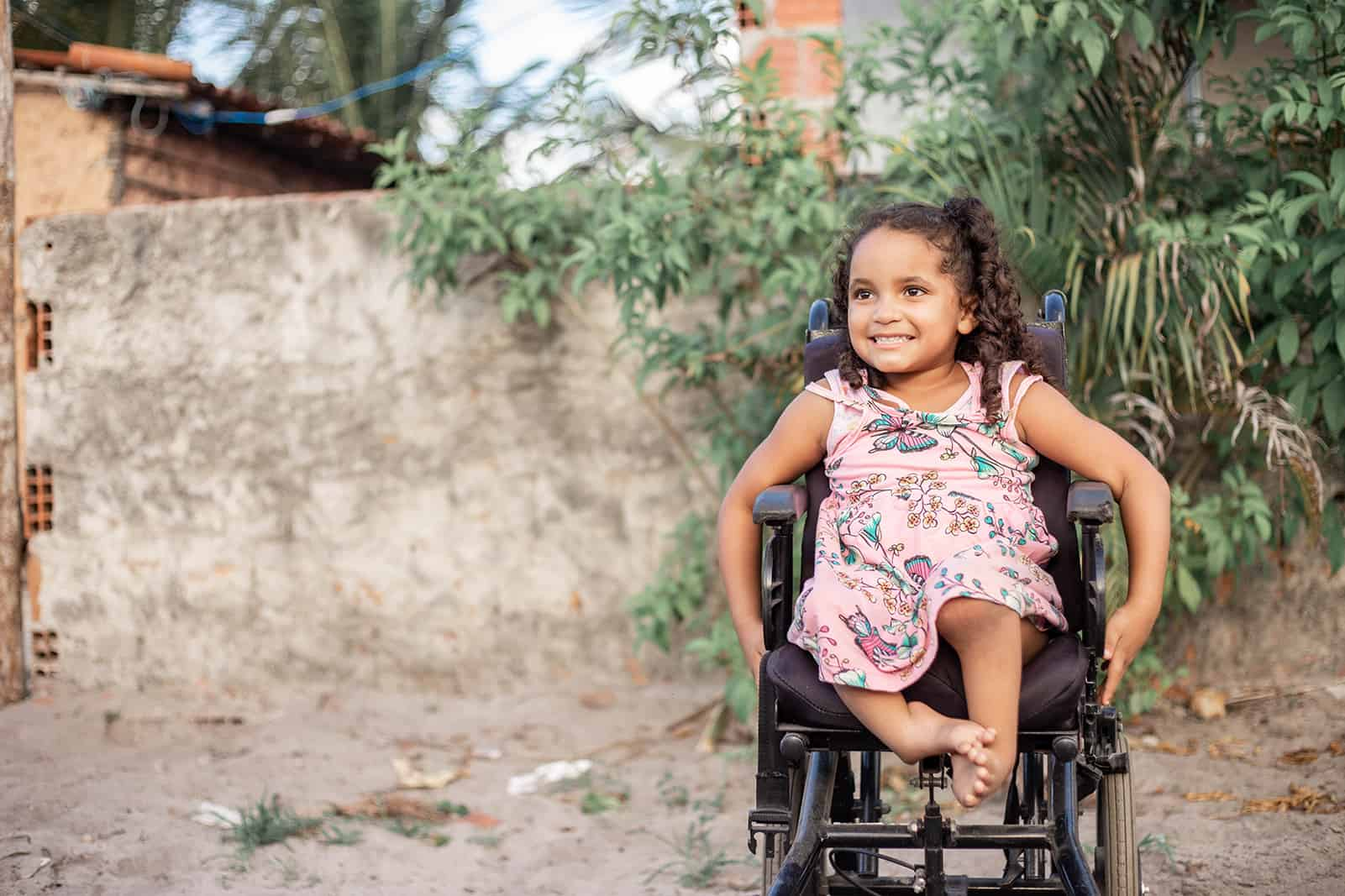 Maisa, in a pink dress, is sitting in her wheelchair on the road outside her house.
